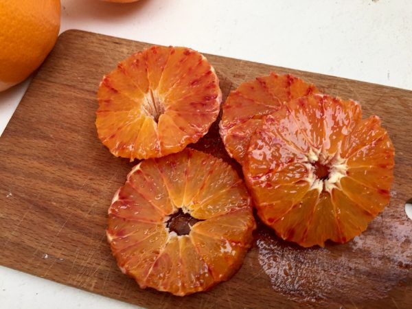 Remove the skin and the pith from the oranges.  Using a very sharp knife, cut out the sections of the oranges, leaving any connecting pith behind.  Alternatively, cut the oranges into thin slices.